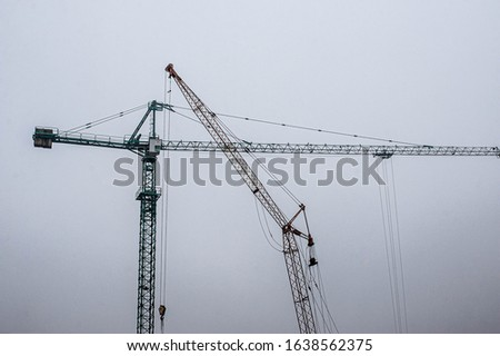 Big tower cranes against foggy sky. Background image of construction equipment. Copy space.