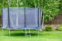 Big trampoline for children and adults. Trampoline with safety net set on green grass beside wooden fence. Green background. Sunny summer day
