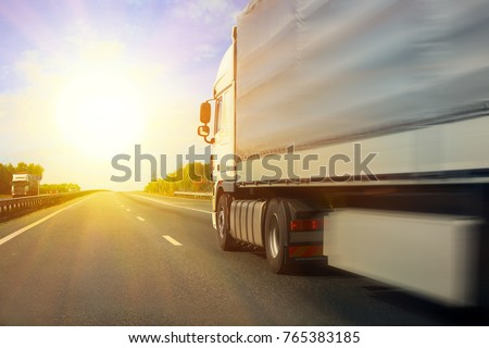 big truck goes on the highway to sunrise
