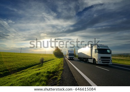 Big truck overtaking a small truck on a road in a rural landscape at sunset with dramatic clouds