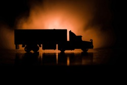 Big truck wagon rides on the road outside the city at night with foggy background. Decoration