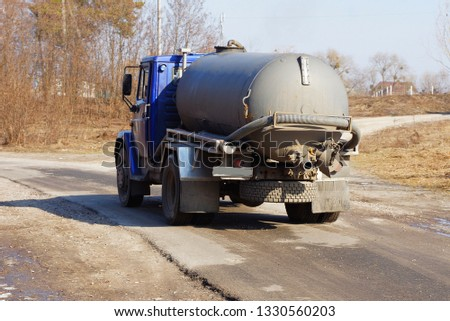 big truck with a gray barrel and a hose goes on an asphalt road