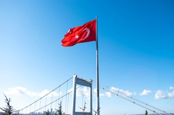 Big Turkish flag in blue sky. Turkish flag rippling in the wind. The giant Turkish flag attached to the big post in front of the Fatih Sultan Mehmet Bridge.