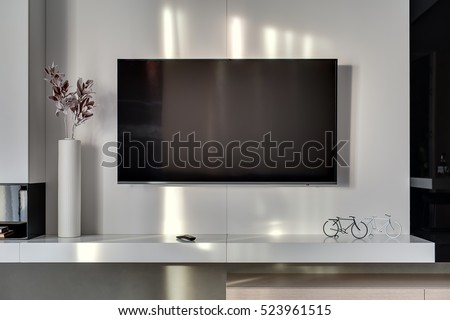 Big TV on the white wall in the room in a modern style. Under it there is a white rack with a flower in a vase, TV remote, decorations in a form of the bicycles. Closeup. Horizontal.
