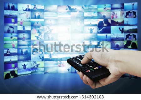 Big TV panel with television stream images and remote control in hand