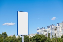 Big vertical billboard with copy space on urban background against blue sky. Advertising space with high-rise building and trees.