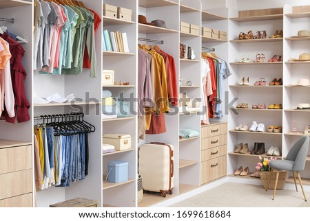 Big wardrobe with different clothes and accessories in dressing room Foto stock ©