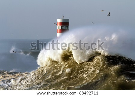 Big wave against beacon and pier in the north of Portugal in a stormy morning - mouth of river Douro, Porto