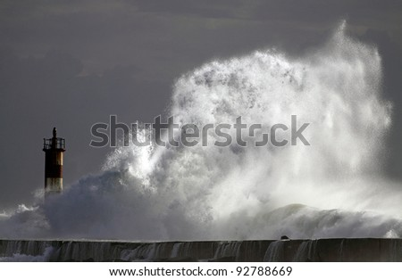 Big wave against lighthouse in the north of Portugal in a stormy overcast evening, with interesting light - mouth of river Ave in Vila do Conde