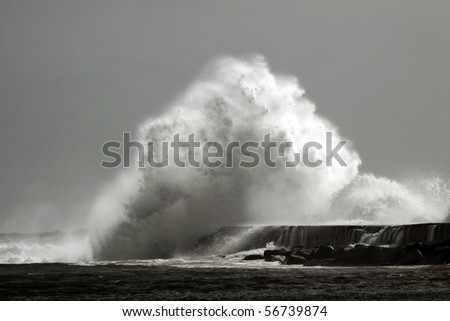 Big wave against little harbor in a stormy day in portuguese coast