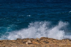 Big wave close up. Rocky beach in St Paul's Bay, Malta at sunny day. Beautiful stormy blue mediterranean sea. Selective focus.