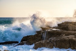 Big wave crashes against the rocks of a coast in the sunlight