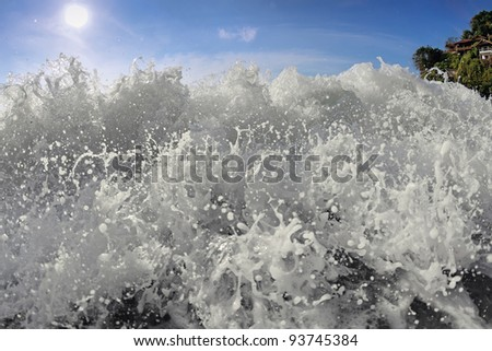 Big wave front with bubbles and splashes closeup view on Koh Phangan, Thailand