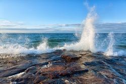 Big wave splash on Lake Superior in the Upper Peninsula of Michigan. Waves break against a rocky shoreline near Pictured Rocks National Lakeshore near Munising