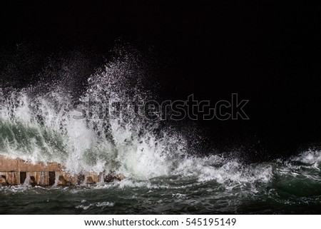 big waves on the breakwater at night