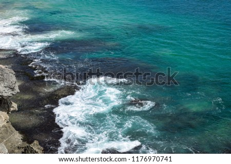 Big waves spotted from a high cliff. Shades of blue turquoise water and white foam #1176970741