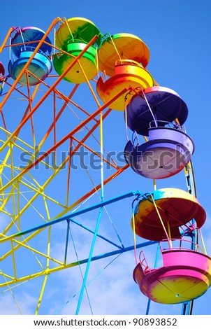 big wheel with multicolored cabins in amusement park