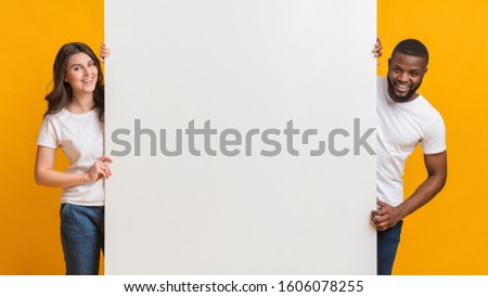 Big White Advertisement Board In Hands Of Happy Interracial Couple That Standing Over Yellow Background, Free Space For Your Text, Panorama