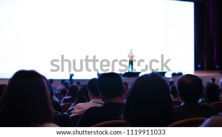 Big White Background Screen Behind Presenter Holding Hands Up. Audience or People. Crowd of Spectators Sitting Facing Speaker and Screen. Man Presenting Lecture to People Sitting in Conference Hall.