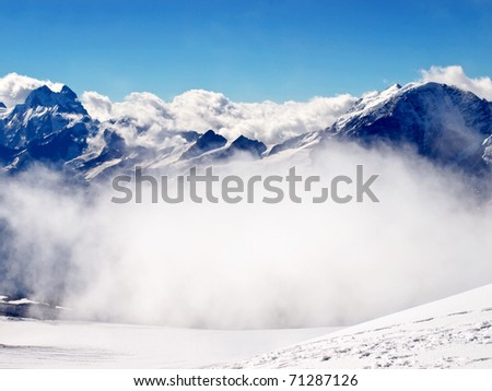 Big white cloud and dark mountains. Natural composition