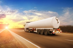 Big white fuel tanker truck shipping fuel on the countryside road in motion against a night sky with a sunset