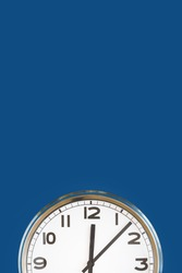 Big white plain wall clock on trending dark blue background. Ten o'clock. Close up with copy space, time management or school concept and summer standard or winter time change, opening hours.