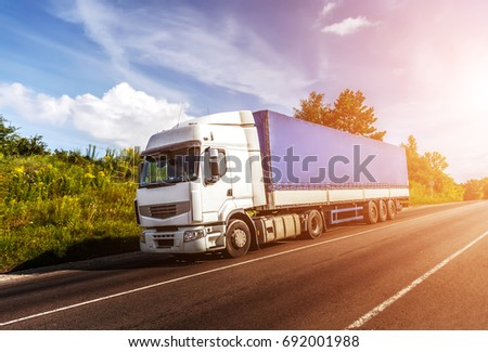 big white truck on the road in a rural landscape at sunlight. perfect sky. over the asphalt road at sunset. logistics transportation and cargo freight transport industrial business commercial concept: #692001988