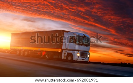 big White Truck on the Road in a Rural Landscape at Sunset. Picturesque Overcast Sky. over the Asphalt Road. Logistics Transportation and Cargo Freight Transport Industrial Business Commercial Concept