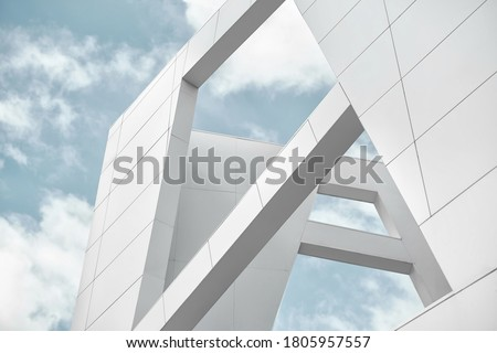 Photo of  Big white walls of the building against the blue sky and white clouds. Modern architecture. Minimalistic design