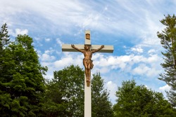 Big white wooden crucifix of Jesus Christ outdoors in a cemetery - bronze sculpture hit by sunlight against a blue sky with white clouds and green trees