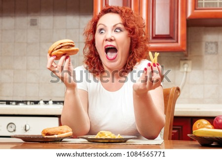 Big woman eat fast food. Red hair fat girl with burger, potato and fruit. Unhealthy food concept with plus size female on kitchen #1084565771