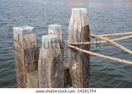 Big wooden bollard with rope of tied ship