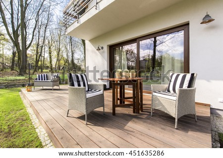 Big wooden cozy porch with chairs and coffee table in the back of big residence #451635286