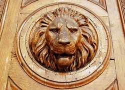 Big wooden head of lion on the front door