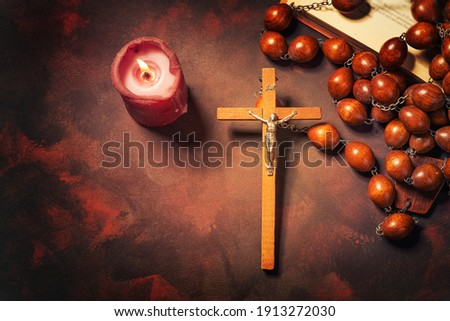 Big wooden Rosary beads and crucifix cross with jesus,red candle and bible book,spiritual atmosphere ,religion concept. Stock photo ©