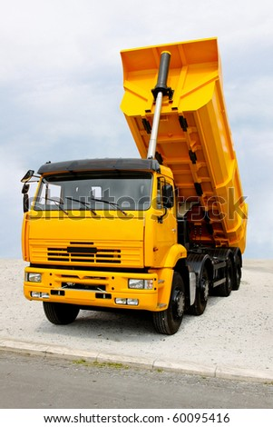 Big yellow construction tipper truck discharging loads