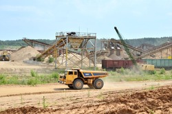 Big yellow dump truck transporting sand in an open-pit. Crushing factory, machines and equipment for crushing, grinding stone, sorting sand and bulk materials. Mining quarry, background
