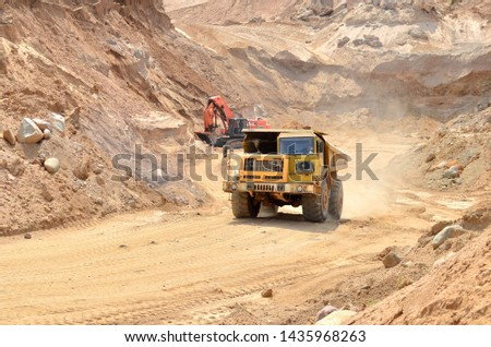 Big yellow dump truck transporting sand in an open-pit mining quarry. Mining quarry for the production of crushed stone, sand and gravel for use in the construction industry - image #1435968263