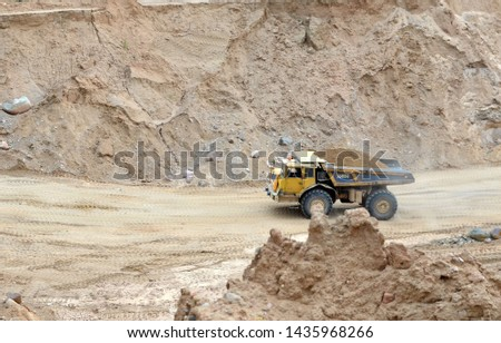 Big yellow dump truck transporting sand in an open-pit mining quarry. Mining quarry for the production of crushed stone, sand and gravel for use in the construction industry - image #1435968266