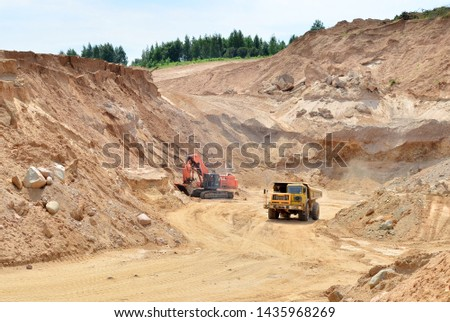 Big yellow dump truck transporting sand in an open-pit mining quarry. Mining quarry for the production of crushed stone, sand and gravel for use in the construction industry - image #1435968269
