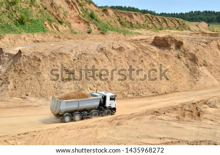 Big yellow dump truck transporting sand in an open-pit mining quarry. Mining quarry for the production of crushed stone, sand and gravel for use in the construction industry - image #1435968272