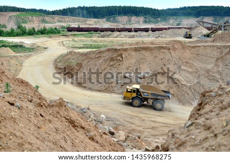 Big yellow dump truck transporting sand in an open-pit mining quarry. Mining quarry for the production of crushed stone, sand and gravel for use in the construction industry - image #1435968275