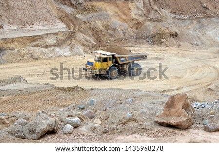 Big yellow dump truck transporting sand in an open-pit mining quarry. Mining quarry for the production of crushed stone, sand and gravel for use in the construction industry - image #1435968278