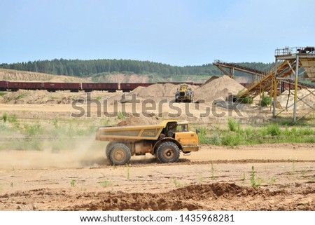 Big yellow dump truck transporting sand in an open-pit mining quarry. Mining quarry for the production of crushed stone, sand and gravel for use in the construction industry - image #1435968281