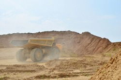 Big yellow dump trucks working in the open-pit. Transporting sand and minerals. Mining quarry for the production of crushed stone, sand and gravel for use in the construction industry - image