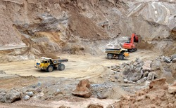 Big yellow dump trucks working in the open-pit. Transporting sand and minerals. Mining quarry for the production of crushed stone, sand and gravel for use in the construction industry