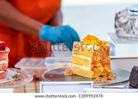 Big yellow orange peach layered cake slice on tray display in street food market or catering bakery cafe with vibrant color and buttercream cream filling layers #1289992474