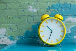 Big yellow retro style alarm clock decorated in a living room with colorful brick wall