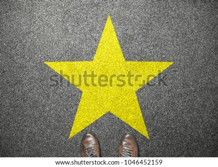 big yellow star on floor with businessman shoes