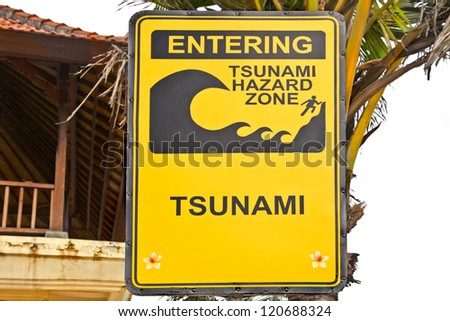 Big yellow tsunami sign on a wooden post on beach in Bali, Indonesia